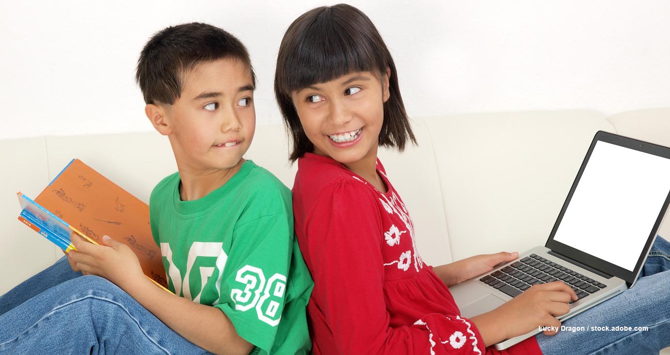 Print und/oder digital? Mädchen mit Notebook und Junge mit Buch